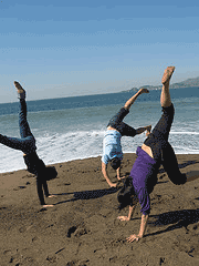 Three people doing handstands on the beach