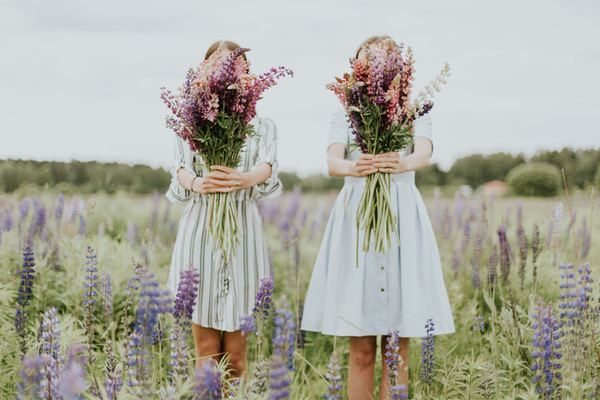 Friend two woman holding pink petaled flowers. Photo by Daiga Ellaby on Unsplash